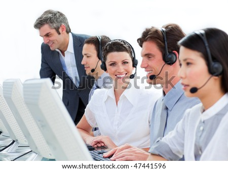 Self-assured mature manager checking his employee's work in a call-center