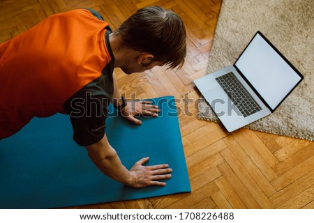 Self-care during stay at home COVID-19 Pandemic. Fitness training, stretching exercises online men at home with laptop. Attractive guy lying on fitness mat online yoga lessons blank laptop screen