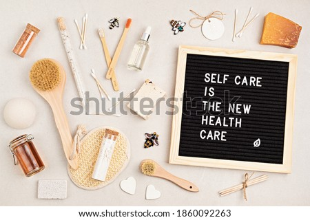 Self care is the new health care. Motivational quote on black letter board with variety of organic body and face care products. Natural homemade eco friendly beauty products concept. Flatlay, top view