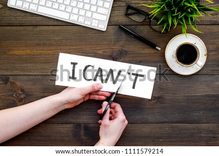 Self confidence concept. Hands cutting the letter t of written word I can't by sciccors. Office desk. Dark wooden background top view copy space Foto stock ©