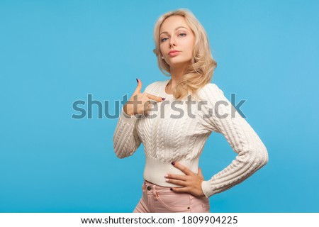 Self confident arrogant woman with curly blond hair pointing finger on herself, bragging with achievements, egoism. Indoor studio shot isolated on blue background Stock fotó ©