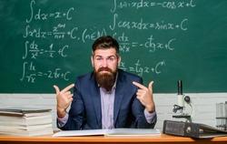 Self confident teacher introducing himself. I know everything. Teacher man pointing himself. Narcissist selfish educator. Superior teacher in classroom. Arrogant school principal looking at camera.