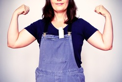 Self-confident woman in dungarees or bip trousers with a folding rule flexing her biceps muscles, filter effect.