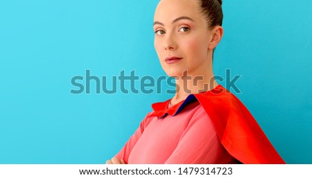 Self-confident woman with crossed hands in red cape looking at camera, super hero on blue background