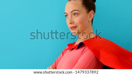 Self-confident woman with crossed hands in red cape, super hero on blue background