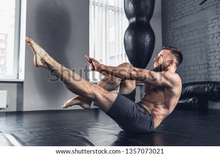 Self-control and motivation. The bare-chested athlete trains hard in the gym, doing strength exercises for abdominal or abs, hand's muscles, work on his upper body. Fitness, sport and healthy concept.
