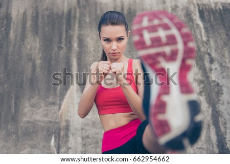 Self defence. Focus of a young cute serious fighter, training kickboxing high kick exercise with her foot, outdoors, in pink fashionable sport outfit, trendy sneakers Stock photo ©