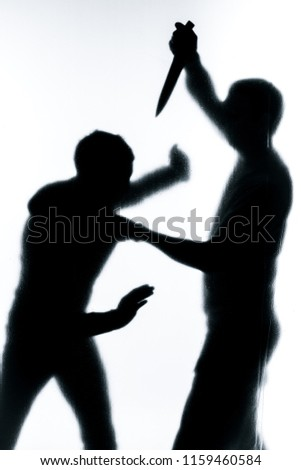 Self-defense battle silhouette. A man fights against an aggressor with a knife. Fight for life against terrorists.