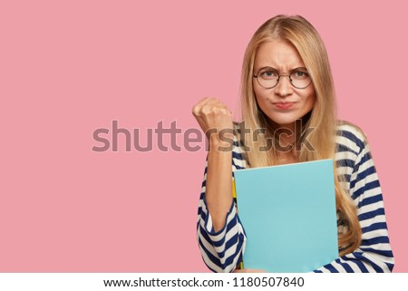 Self determined beautiful woman keeps hand raised in fist, has displeased facial expression, warns you, demonstrates her strength and power, wears round transparent glasses, copy space aside #1180507840