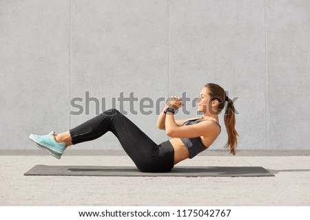 Self determined sporty woman with pony tail, dressed in leggings, top, sneakers, smartwatch makes on press, wants to have muscular body, has workout in in gym. People, gym and sport concept. #1175042767