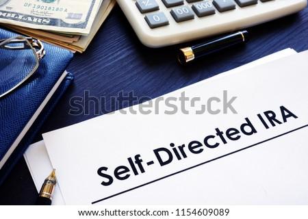 Self-Directed IRA SDIRA documents on a desk. #1154609089