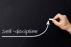 Self discipline concept. Hand with chalk drawing rising arrow. Discipline and self motivation