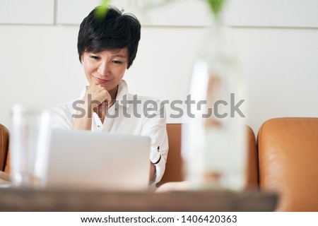 self employed asian woman sitting on couch & working on laptop at home