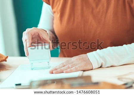 Self employed female carpenter is stamping project documentation in small business woodwork workshop, close up of hands