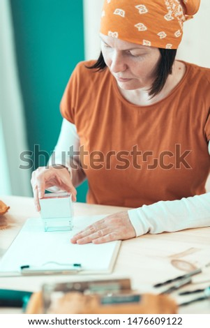 Self employed female carpenter is stamping project documentation in small business woodwork workshop