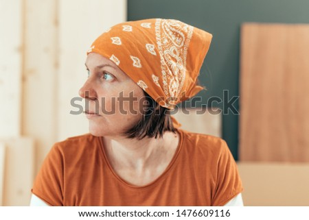 Self employed female carpenter looking out the window portrait in her small business woodwork workshop