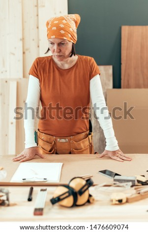 Self employed female carpenter planning DIY project in her small business woodwork workshop