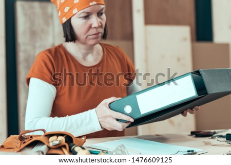 Self employed female carpenter with document ring binder in small business woodwork workshop, selective focus