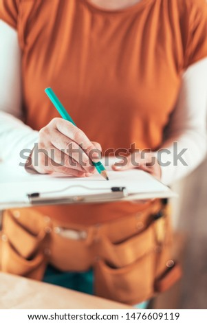 Self employed female carpenter writing project notes on clipboard notepad paper in small business woodwork workshop