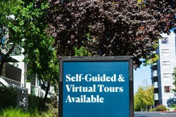 Self-Guided and Virtual Tours Available advertisement sign near a luxury apartment building.