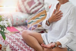 Self-Healing Heart Chakra Meditation. Woman sitting in a lotus position with right hand on heart chakra and left palm open in a receiving gesture. Self-Care Practice at Home