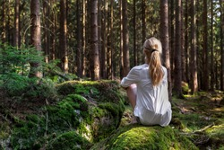 Self-isolation in the open air. Girl sitting alone in green forest enjoys the silence and beauty of nature.