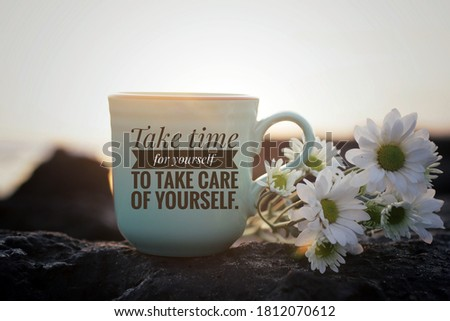 Self love inspirational motivational words - Take time for yourself to take care of yourself. Cup of morning tea or coffee with flowers on sea rock in the beach on background of sunset sunrise light.