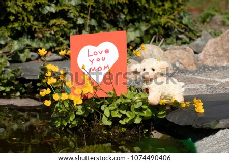 "Self made card, white heart on red background and a cute little sheep. On card is written ""Love You Mom"". Concept Mothers day. Outdoor. #1074490406"