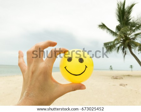 Self Made Hand Drawing Happy Smiley Face on Yellow Ball with  Summer Beach View on  Peaceful Island