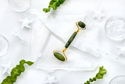Self made moisturizer and green jade face roller with pieces of ice. Exotic fern leaves and water drops on off white background. Monochromatic white green look. Facial massage, handmade cosmetics.