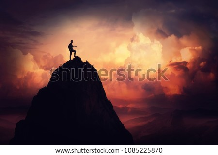 Self overcome concept as a businessman climbing a tall mountain over the clouds. Road to win and succes over sunset background. Achieving goals symbol.