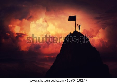 Self overcome concept as a businessman lift his hands up on the top of al mountain reaching the finish flag. Road to win and success over sunset background. Goal achievement symbol.