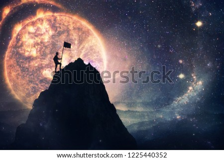 Self overcome concept as a man leader climbing a tall mountain carrying a flag to the top. Road to win and success over starry night sky cosmic background. Achieving goals symbol.