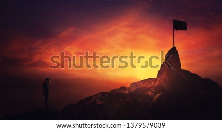 Self overcome concept, climber man hand to forehead looking attentive to horizon finding the finish flag. Road to achieve success over sunset sky background. Life quest obstacles, reaching goals. #1379579039