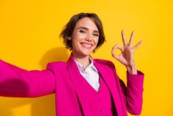 Self-portrait of attractive cheerful girl showing ok-sign advert ad isolated over bright yellow color background