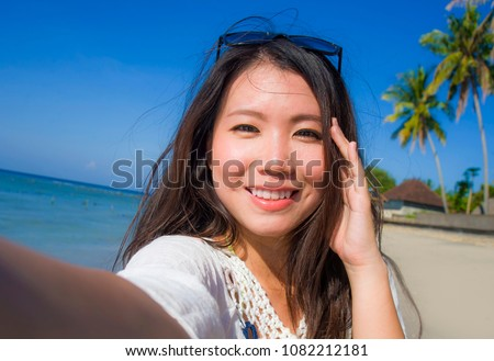 self portrait of gorgeous beautiful and happy Asian Korean or Chinese woman 20s taking selfie photo with mobile phone camera in exotic tropical beach enjoying summer holidays trip smiling cheerful