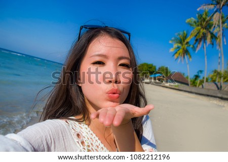 self portrait of gorgeous beautiful and happy Asian Korean or Chinese woman 20s taking selfie photo sending kiss with mobile phone camera in exotic tropical beach enjoying summer holidays trip
