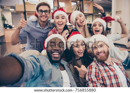 Self portrait of mixed race unity of african, american, asian, caucasian friends, happy bearded men and beautiful women in red santa hat showing thumb up, like, ok gesture to the camera in office