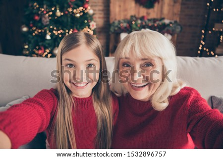 Self-portrait of nice attractive lovely charming glad cheerful cheery granny pre-teen grandchild spending wintertime vacation day at decorated industrial loft style interior house
