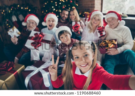 Self-portrait of noel family gathering. Grey-haired grandparents, granddaughter, grandson, grandchildren, brother, sister keeping, getting gifts, showing two fingers, peace symbol, v-sign, fun joy