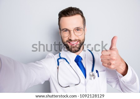 Self portrait of positive trendy doc in white outfit with tie and bristle having stethoscope on his neck shooting selfie showing thumb up, like sign with finger, hand over grey background #1092128129