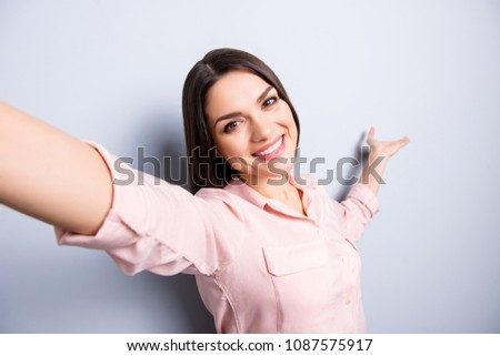 Self portrait of pretty charming cheerful woman shooting selfie on front camera gesturing with palm copy space empty place on palm isolated on grey background