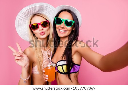 Self portrait of sexy, joyful, dreamy, charming, hot, stylish, pretty tourists shooting selfie on front camera, showing two fingers with pout lips, having alcohol beverage, isolated on pink background