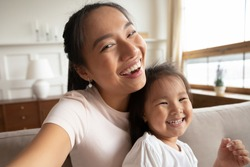 Self-portrait picture of happy Vietnamese young mom or nanny with cute little biracial girl child pose together, selfie of overjoyed Asian mother have fun play with small ethnic daughter at home