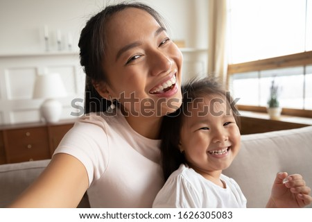 Self-portrait picture of happy Vietnamese young mom or nanny with cute little biracial girl child pose together, selfie of overjoyed Asian mother have fun play with small ethnic daughter at home stock photo