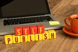 Self Publish written on a wooden cube in a office desk