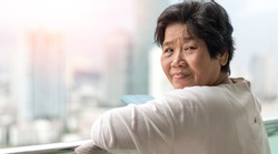 Self quarantine in senior concept. Asia old woman standing at balcony stay at home in urban city for self-isolation social distancing to protect from pandemic COVID-19 or novel coronavirus.