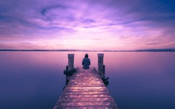 Self reflection in magical world of fantasy. One woman sits on a wooden pier. Cloudy above the lake. Long exposure
