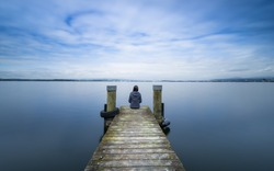 Self reflection.  Woman sits on a wooden pier. Cloudy above the lake. Long exposure.