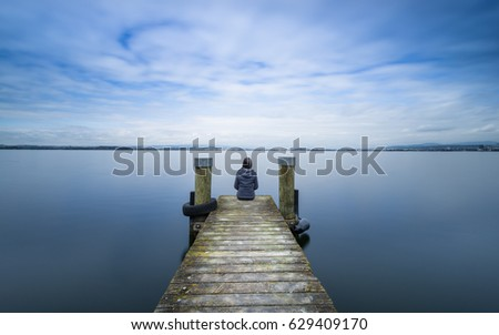 Self reflection.  Woman sits on a wooden pier. Cloudy above the lake. Long exposure. #629409170
